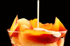 Peaches and Cream. Fresh peach slices in a dessert bowl, with cream drizzling down. Black background royalty free stock image