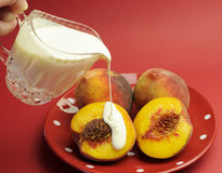Peaches and Cream Complexion concept. With plate of fresh yellow peaches with pouring glass crystal jug of cream, against a red background Stock Images