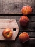Peaches. On cutting board and wooden table Stock Photo