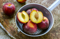 Peaches in  dipper in the old surface. Rustic style Royalty Free Stock Photos