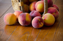 Peaches falling out of a basket Royalty Free Stock Photography