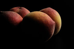 Peaches,four peaches with black background Stock Images