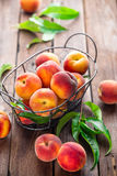 Peaches. Fresh peaches with leaves on wooden background Stock Photography