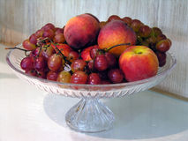 Peaches and grapes in bowl. Glass fruit bowl with peaches and red grapes Royalty Free Stock Photos