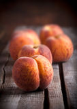 Peaches group on old wooden table. Peaches group on old rustic wooden table and dark background Royalty Free Stock Photos