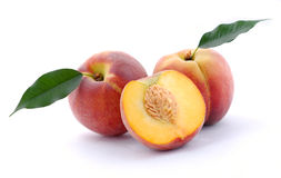 Peaches and a half and leaves Royalty Free Stock Photos