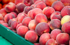 Peaches. A large pile of fresh peaches in a green wood bin at the Clement Street Farmers Market in San Francisco stock photo