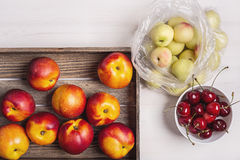 Peaches, nectarines and cherries on a white background. Still-life with fruit on a white table stock photography