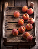 Peaches in old rustic wooden box. On wooden table Stock Photo