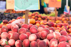 Peaches and other fruits. Bins of peaches, plums and nectarines at the Clement Street Farmers Market in San Francisco. Colorful signs and cut samples stock photo