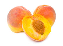 Peaches and a peach half Royalty Free Stock Image