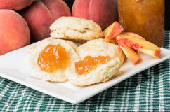 Peaches with peach jam and biscuits Stock Images