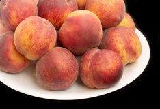Peaches on plate isolated on black Stock Image