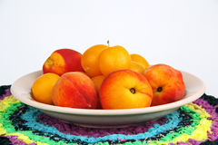 Peaches and plums in a bowl. Some peaches and yellow plums in a bowl on a colored napkin Royalty Free Stock Image