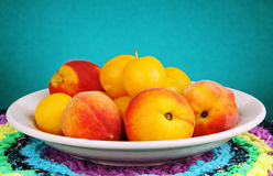 Peaches and plums in a bowl. Some peaches and yellow plums in a bowl on a colored napkin Royalty Free Stock Images