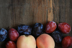 Peaches and plums on dark wooden table. Stock Photos