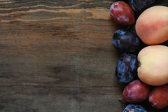 Peaches and plums on dark wooden table. Stock Images