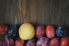 Peaches and plums on dark wooden table. Royalty Free Stock Photo