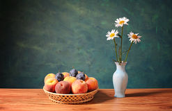 Peaches and plums in wicker baskets and flowers Royalty Free Stock Image