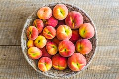 Peaches Prunus persica and flat saturn or doughnut peach platycarpa in a grey rattan bowl royalty free stock photo
