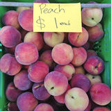 Peaches for sale $1 at farmers market Stock Photos