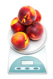 Peaches on the scales on a white Stock Image