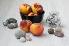Peaches with sea pebbles. Juicy peach with sea pebbles in a glass jar Royalty Free Stock Photos