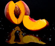 Peaches shot against black and givingreflect Royalty Free Stock Image