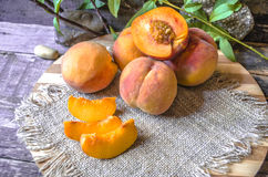 Peaches with slices on a cutting board covered sackcloth Royalty Free Stock Image
