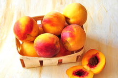 Peaches are in a small basket Stock Images