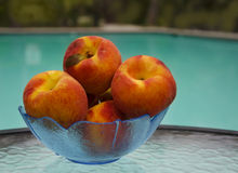 Peaches by the swimmimg pool. Peaches in a glass plate on table by the swimming pool Stock Photos