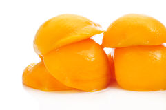 Peaches in syrup. Some peeled and halved peaches in syrup on a white background Royalty Free Stock Images