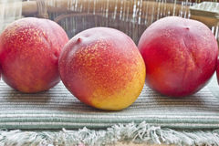 Peaches on the table. Three ripe peaches on a glass table Royalty Free Stock Photos