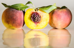 Peaches. Three peaches in line. Middle one is cut on half Stock Photos