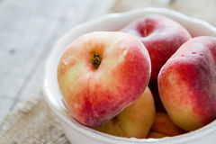 Peaches in white bowl Stock Photo