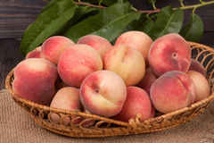 Peaches in a wicker basket with leaves on wooden table.  royalty free stock image