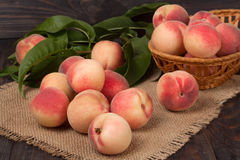 Peaches in a wicker basket with leaves on wooden table.  royalty free stock photography