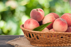 Peaches in a wicker basket on wooden table with blurred background. Peaches in a wicker basket on a wooden table with a blurred background royalty free stock images