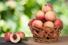 Peaches in a wicker basket on wooden table with blurred background. Peaches in a wicker basket on a wooden table with a blurred background royalty free stock photo