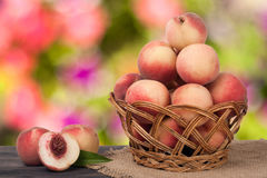 Peaches in a wicker basket on wooden table with blurred background. Peaches in a wicker basket on a wooden table with a blurred background royalty free stock photography