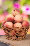 Peaches in a wicker basket on wooden table with blurred background. Peaches in a wicker basket on a wooden table with a blurred background stock photos