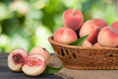 Peaches in a wicker basket on wooden table with blurred background. Peaches in a wicker basket on a wooden table with a blurred background stock photo