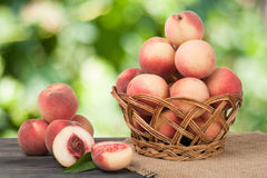 Peaches in a wicker basket on wooden table with blurred background. Peaches in a wicker basket on a wooden table with a blurred background royalty free stock image