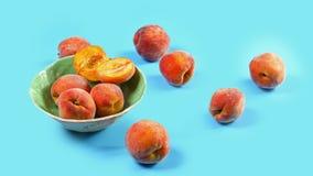Peachs maduros de la fruta en un fondo del azul de la placa Concepto local de la producción de la cosecha estacional de la cosech fotografía de archivo libre de regalías