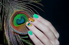Peacock feather and green nail art. In inverted colours Stock Photography