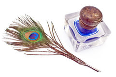 Peacock feather quill and inkwell Stock Image