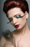 Peacock make-up. Close-up portrait of young woman with peacock feather royalty free stock images