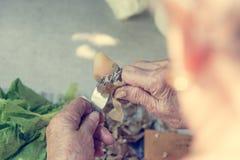 peaing potatoe的年长手特写镜头  免版税图库摄影