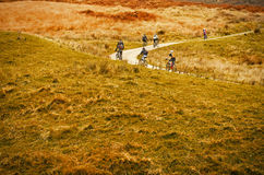 Peak District National Park, England, Europe. Group of riders cyclists riding uphill one behind other during  race. Royalty Free Stock Image