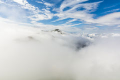 Peak emerging from the whirl of clouds Stock Images